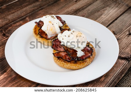 Benedict eggs with crispy bacon and hollandaise sauce on toasted Maffin on clean plate - stock photo
