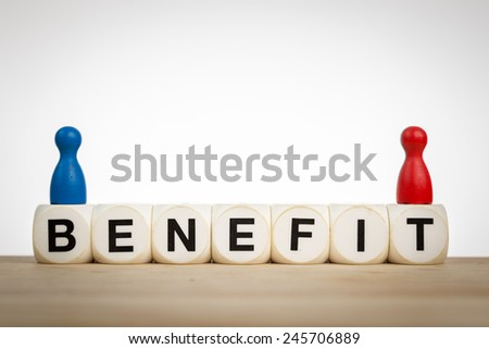 Benefit concept: Two pawns on top of of toy dice - stock photo