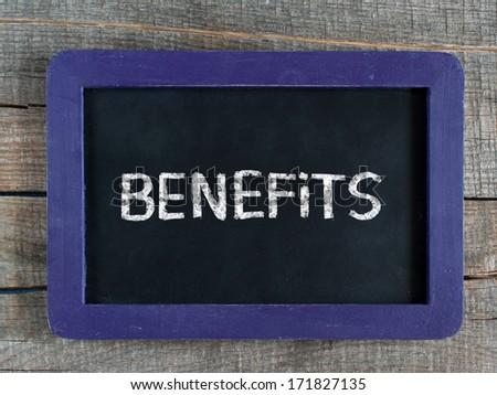 Benefits word written on blue framed chalkboard on wooden background - stock photo