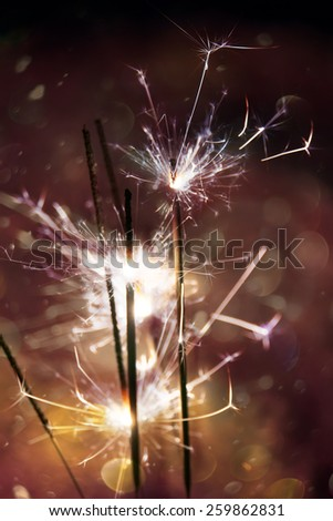 Bengal fire, sparkler and colorful bokeh with blurred snow, christmas, new year background. - stock photo