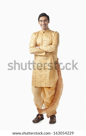 Bengali man standing with his arms crossed and smiling - stock photo