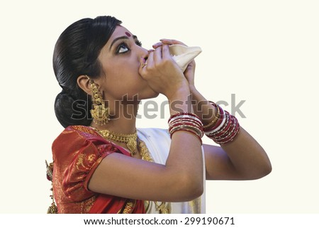 Bengali woman blowing on a conch shell - stock photo