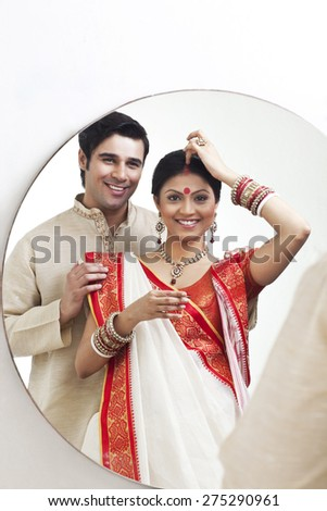 Bengali woman putting sindoor on her forehead while husband watches on - stock photo
