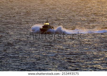 Benghisa, Birzebbuga, Malta February 16, 2015: Armed Forces of Malta Patrol Boat P22 patrolling the west coast in the warm light of the setting sun. - stock photo