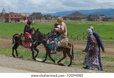 BENI MELLAL, MOROCCO - APRIL 16: Berber family riding on donkeys, April 16 2010 in Beni Mellal near Marrakesch in the Atlas Mountains, Morocco. - stock photo