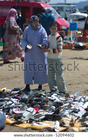 BENI MELLAL, MOROCCO - APRIL 16: Mother and son looking for shoes on a souk (market) April 16 2010 in Beni Mellal near Marrakesch, Morocco. - stock photo