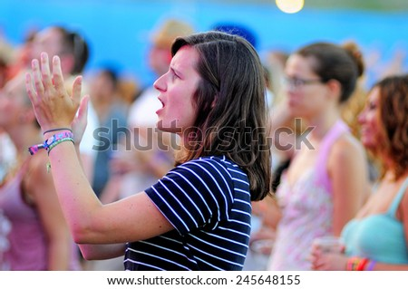 BENICASSIM, SPAIN - JULY 19: A woman from the crowd applauding at FIB (Festival Internacional de Benicassim) 2013 Festival on July 19, 2013 in Benicassim, Spain. - stock photo