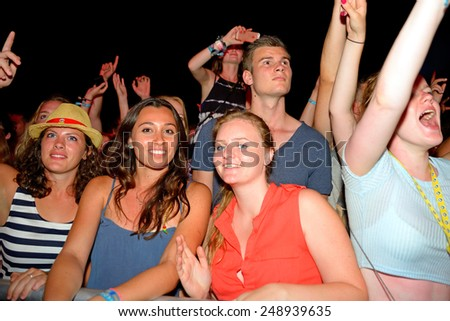 BENICASSIM, SPAIN - JULY 19: Women watch a concert in the crowd at FIB Festival on July 19, 2014 in Benicassim, Spain. - stock photo