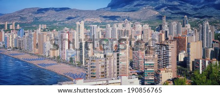 Benidorm, Costa Blanca - a coastal town and popular touristic resort in province of Alicante, Spain. Aerial view of city skyline formed by tall hotels and apartment buildings and mountains