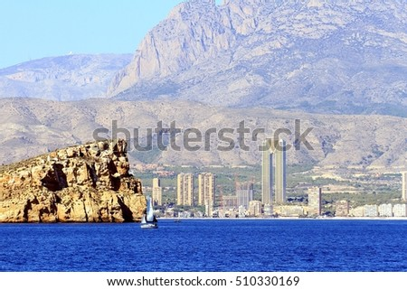 Benidorm island with sailing boat along the coast of Alicante and the skyscrapers of Benidorm city,