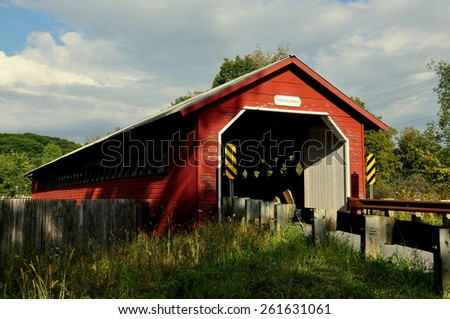 Bennington, Vermont  - September 17, 2014 :  Red wooden 1889 truss and lattice Paper Mill Covered Bridge over the Walloomsac River - stock photo