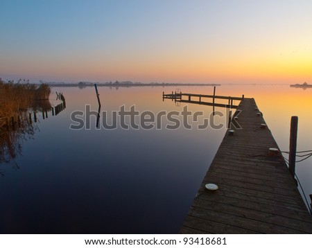 Bent jetty during sunset over lake - stock photo
