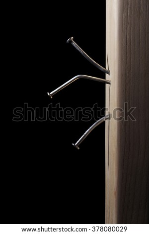 Bent Nails in Wood on a Black Background - stock photo