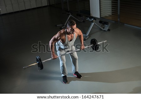 Bent Over Barbell Row. Man Doing Heavy Weight Exercise For Back - stock photo