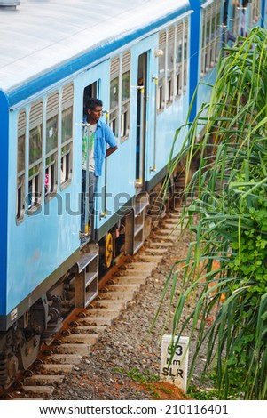 BENTOTA, SRI LANKA - 28 APR 2013: Man stay in a door of a blue train in Bentota, Sri Lanka. Trains are becoming more popular transport last years due to railway improvement by government - stock photo