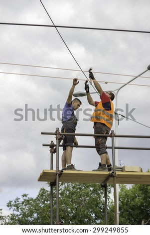 BEOGRAD, SERBIA - JULY 14, 2015:  Workers installing the tram supply power system. Overhead line electrification for new tram system.. Selective focus and shallow dof.