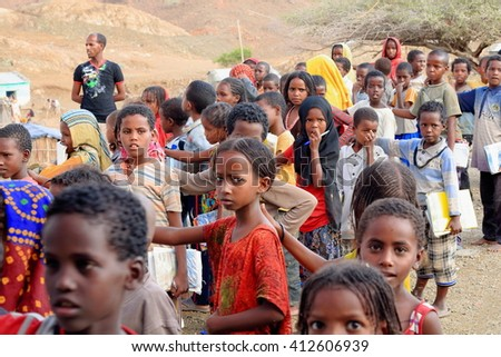 BERAHILE, ETHIOPIA-MARCH 29, 2013: Schoolgirls and boys queue up on the playground to enter their classroom-textbooks and notebooks in hand at the Berahile town school on March 29, 2013. Afar region.