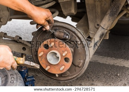 BERASTAGI, SUMATRA June 18, 2014: our driver repairs the broken brake - stock photo