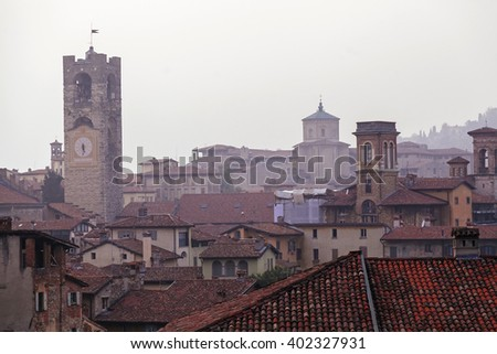 Bergamo bell tower and house roofs in fog