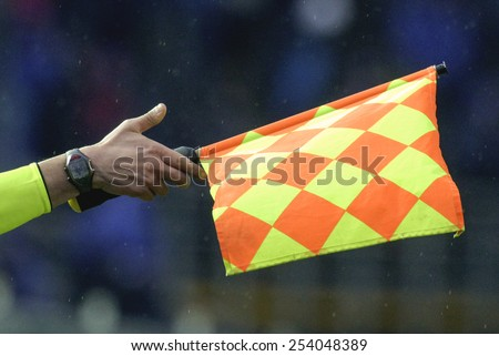 BERGAMO-ITALY-FEBRUARY 15,2015: linesman and assistant referee waving flag during the italian soccer match Atalanta vs FC Internazionale, in Bergamo. - stock photo