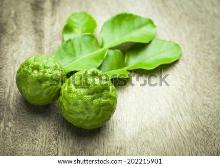 Bergamot fruit with green leafs on wood background - stock photo