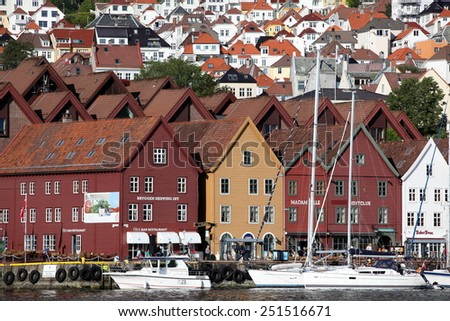 BERGEN, NORWAY - CIRCA JULY 2012: Tourists and locals stroll along the UNESCO World Heritage Site, Bryggen, July 2012 in Bergen. Bergen is the second largest city in Norway Population (2013) - 268,700 - stock photo