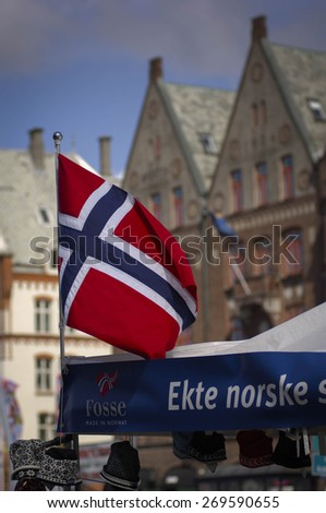 BERGEN/NORWAY 10TH JULY 2006 Norwegian flag with Bryggen behind - stock photo