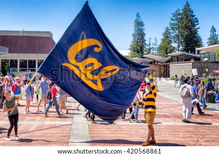 BERKELEY, CA- Apr 16, 2016: University students raise a large school flag in a show of school spirit on Cal Day, an annual campus open house for students, alumni and community visitors. - stock photo