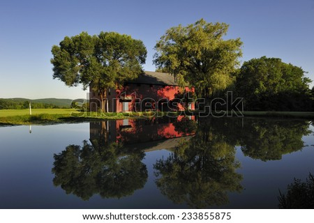 Berkshires, MA, USA -July. 26. 2010: Traditional red barn with beautiful reflection on the pond in Berkshires, state of Massachusetts, USA - stock photo