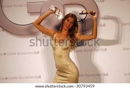 """BERLIN - APRIL 29 : Top Model Gisele Buendchen smiles while presenting a new series of shoes named """"G2B"""" at Hotel Adlonin April 29, 2009 in Berlin. - stock photo"""