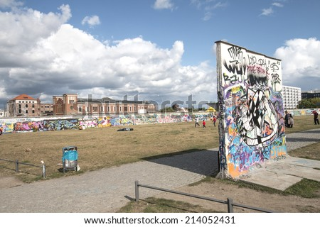 BERLIN - AUGUST 24, 2014 : The East Side Gallery is the largest outdoor art gallery in the world. This photo shows the former death strip with wall segments - stock photo