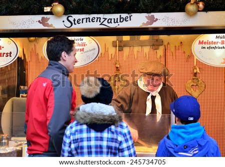 BERLIN, DECEMBER-22, 2014: Tourists waiting for preparation of Christmas traditional dishes on Christmas market in Berlin - stock photo