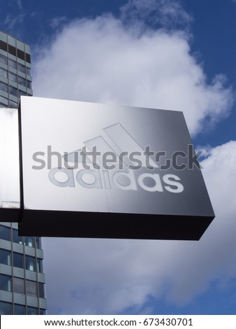 BERLIN, GERMANY - APRIL 8, 2017: Glossy Adidas Logo In Front of A Store In Berlin With A Blue Cloudy Sky