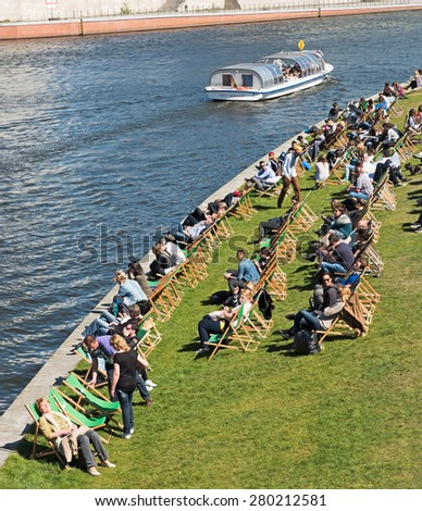 Berlin, Germany - April 14, 2015: People on deck chairs at the beach bar at the main station - stock photo