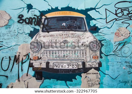 BERLIN, GERMANY - AUGUST 6 2015: Berlin Wall graffiti Trabant. The East Side Gallery is an international memorial for freedom. It is a 1.3 km long section of the Berlin Wall located near the centre. - stock photo