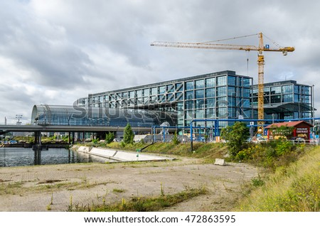 Berlin, Germany - August 14, 2016: East site of the Berlin Central Station (Berlin Hauptbahnhof) with curved glass roof, its Currywurst Fast Food Stand and a crane