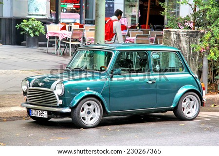 BERLIN, GERMANY - AUGUST 16, 2014: Green classic compact car Austin Mini Cooper at the city street. - stock photo