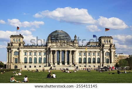 BERLIN, GERMANY - AUGUST 25, 2013: View of the German Parliament, called Der Reichstag. The meadow in front is a very popular place for sunbathes. You see many people in the background walking by.