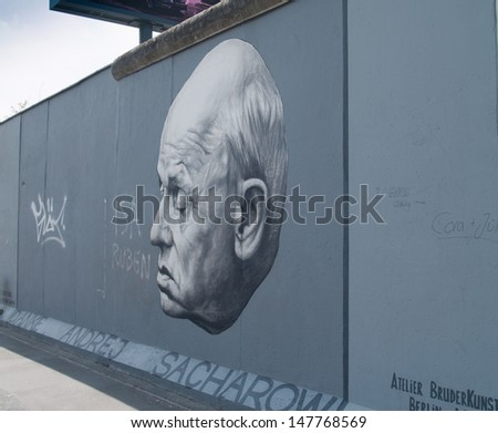 BERLIN, GERMANY - CIRCA JUNE 2013 - Part of the East Side Gallery famous graffiti of academician Andrei Sakharov on Berlin Wall at East Side Gallery. CIRCA JUNE 2013.