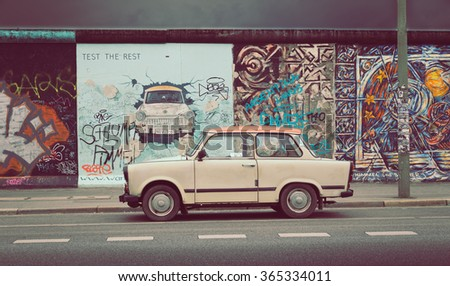 BERLIN, GERMANY - JULY 12: Berliner Mauer (Berlin Wall) at East Side Gallery with an old Trabant, the most common car used in East Germany, on July 12, 2015 in Berlin Friedrichshain-Kreuzberg, Germany - stock photo