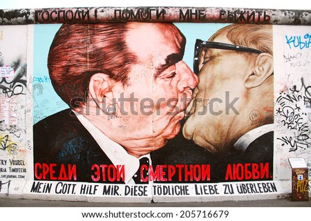 BERLIN, GERMANY - JULY 2, 2014: Fragment of the East Side Gallery exhibition, the largest outdoor art gallery in the world, painted on the segment of Berlin wall  - stock photo
