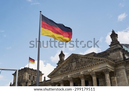 BERLIN, GERMANY - JULY 08: German flag blowing in the wind in front of the Reichstag building. July 08, 2015 in Berlin. - stock photo