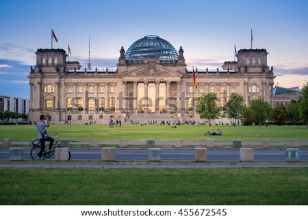 BERLIN, GERMANY - JULY 19, 2016: People sitting on the lawn near the Reichstag building, where the German Parliament - Bundestag sits