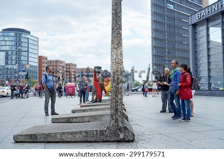 BERLIN, GERMANY - JULY 08: Tourists looking at remaining segments of the wall in central East Berlin. July 08, 2015 in Berlin. - stock photo