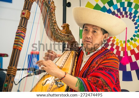 BERLIN, GERMANY - MARCH 8, 2014: genuine original man playing harp at Ecuador stand during ITB Travel Trade Show in the fairgrounds of Messe Berlin. Soft focus on the face of the performer - stock photo