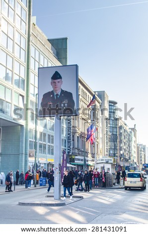 BERLIN, GERMANY, MARCH 12, 2015: people are admiring famous checkpoint charlie which used to serve as a border crossing between west and east germany. - stock photo