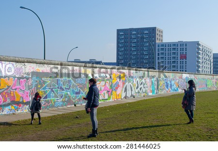 BERLIN, GERMANY, MARCH 12, 2015: people are admiring wall paintings situated on the east side gallery in berlin. - stock photo