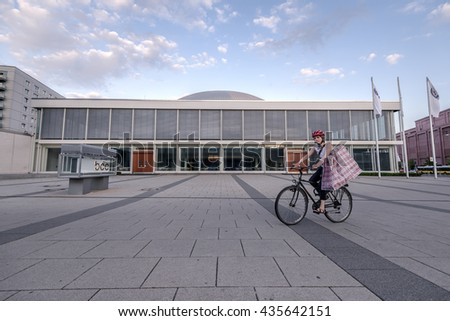 Berlin, Germany - May 11, 2016: A woman on a bike with huge shopping bag passing by near the Berlin Congress Centre.