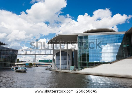 Berlin, Germany, May 12 2013: Tourists ship float on the river Spree next to a modern buildings of Bundestag and Marie-Luders-Haus