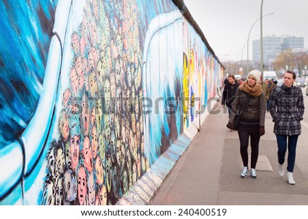 BERLIN, GERMANY - NOV 15, 2014: People walkingat Berlin Wall at East Side Gallery . It's a 1.3 km long part of original Wall which collapsed in 1989 and now is largest world graffiti gallery.  - stock photo